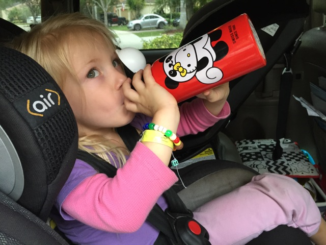 kid in car with water bottle