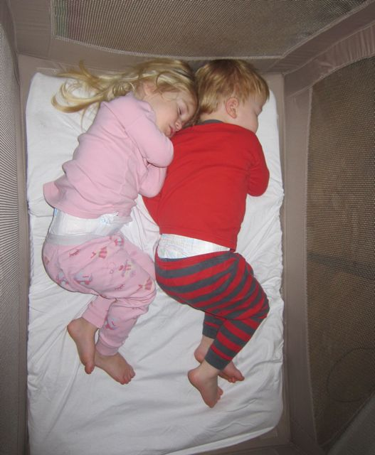 twins sleeping together in crib