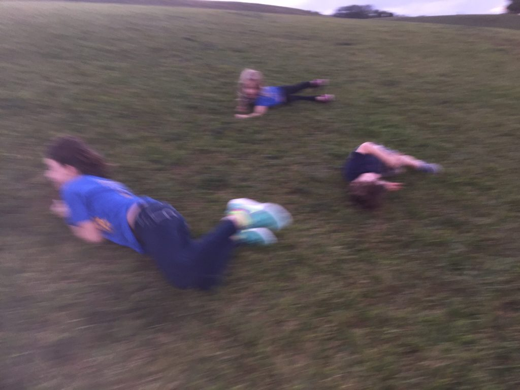kids-rolling-down-hill